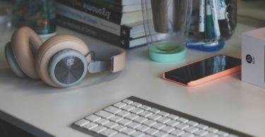 grey and white computer keyboard beside grey headphones