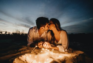 man and woman kissing on brown sand during night time